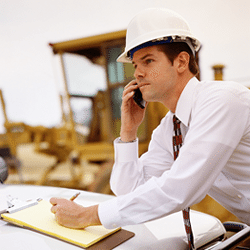 a construction project manager at the phone, taking notes
