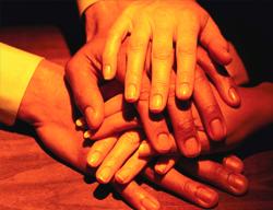 Los miembros del equipo unen las manos, signo de espíritu de equipo