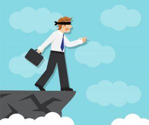 Un hombre de negocios está a punto de caer en un barranco, con los ojos vendados